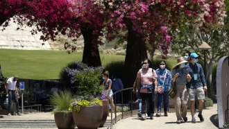 Visitors wear mask while walking through a garden