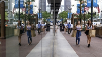 Shoppers reflected in a retail store's windows.
