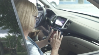 Woman scrolls through her phone