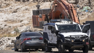 Israeli police tow a car that was said to be used in an attack near Hizmeh Junction in the West Bank, Wednesday.