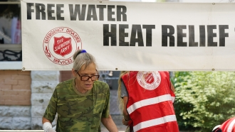 A pedestrian takes a bottle of water at a Salvation Army hydration station during a heatwave as temperatures hit 115-degrees
