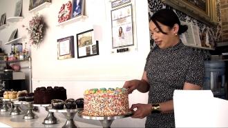 Jenni Vee, Trans Bakery Owner of Jennivee Bakery, slices her Rainbow Pride Cake