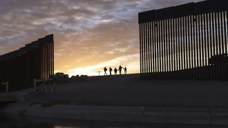 A pair of migrant families from Brazil pass through a gap in the border wall to reach the U.S. and seek asylum