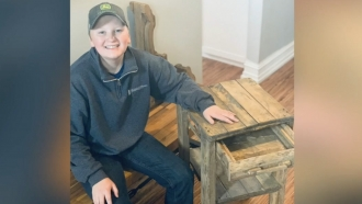 Boy sits next to a wooden nightstand