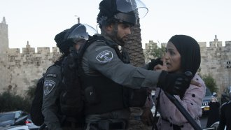 An Israeli border police officer faces off with a Palestinian woman