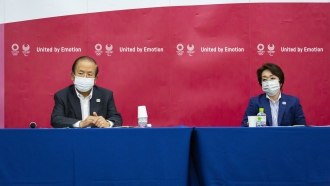 Toshiro Muto and Seiko Hashimoto attend a news conference after receiving a report from a group of of disease experts.