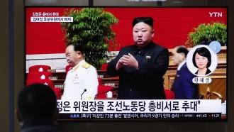 A man watches a TV screen showing a footage of North Korean leader Kim Jong Un.