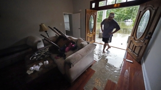 Danny Gonzales walks in his flooded house as water recedes after Tropical Storm Claudette passed through Slidell, La.
