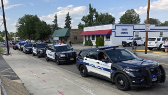 About 30 police cars line up for a procession in honor of an officer who was fatally shot in Arvada, Colorado
