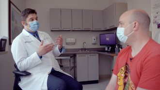 Dr. Marc Sala sits with Patrick Malia, who has had COVID long haul symptoms for more than 460 days.