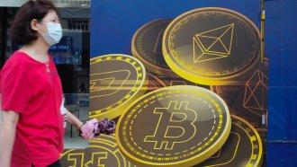 A woman walks past an advertisement for Bitcoin in Hong Kong