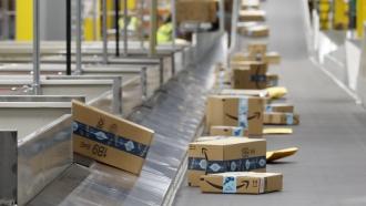 Amazon packages move along a conveyor at an Amazon warehouse facility in Goodyear, AZ.