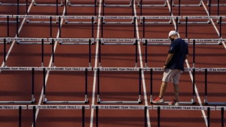 Worker prepares the track for the women's 100-meter hurdles at the U.S. Olympic Track and Field Trials.