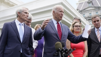 President Joe Biden is joined by a bipartisan group of senators outside the White House.