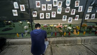 Memorial with donated flowers and candles show photos of missing people near the site of a condo building that collapsed