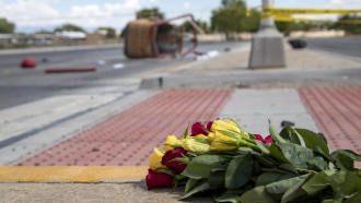A bouquet of flowers from a mourner is placed near the basket of a hot air balloon that crashed in Albuquerque, New Mexico