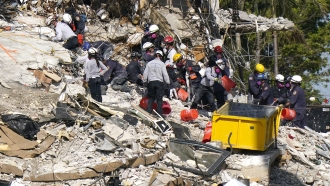 Rescue workers search in the rubble