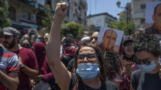 Angry demonstrators carry pictures of Nizar Banat, an outspoken critic of the Palestinian Authority who died in custody.