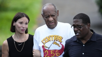 Comedian Bill Cosby, center, and spokesperson Andrew Wyatt, right, approach media gathered outside Cosby's home