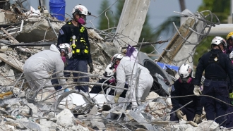 Rescue workers handle a tarp containing recovered remains at the site of the collapsed Champlain Towers South condo building.