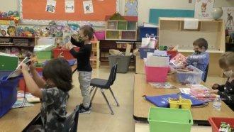 Masked children inside a classroom.