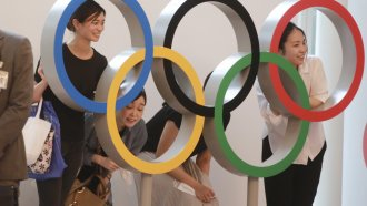 People pose with the Olympic Rings