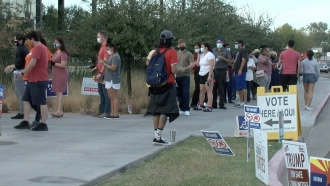 Voters stand in line.