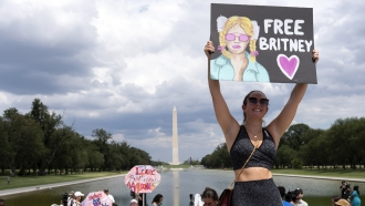 """A woman holds a """"Free Britney"""" sign at a protest against Britney Spears' conservatorship in Washington D.C."""