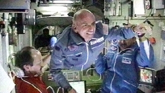 Space station commander Yury Usachev, left, welcomes California millionaire Dennis Tito, center, to the space station