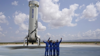 Jeff Bezos and crew with the booster that blasted them into space