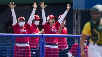 Japanese players celebrate a run scored by Minori Naito.
