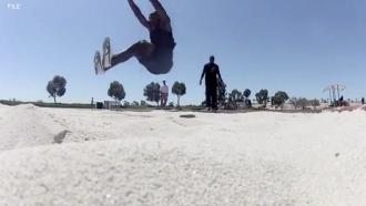 Man jumps into a sandpit.