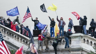 Rioters wave flags on the West Front of the U.S. Capitol in Washington.
