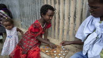 A little girl plays a game of checkers using soda bottle tops with friend at a center for center for displaced Tigrayans.