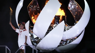 Japan's Naomi Osaka reacts after lighting the cauldron during the Olympics opening ceremony.