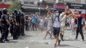 Protesters face Tunisian police officers during a demonstration in Tunis, Tunisia, Sunday, July 25, 2021.