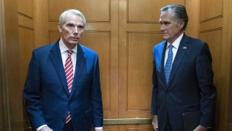 Sen. Rob Portman, R-Ohio, left, accompanied by Sen. Mitt Romney, R-Utah, leave in the elevator after a closed door talks.