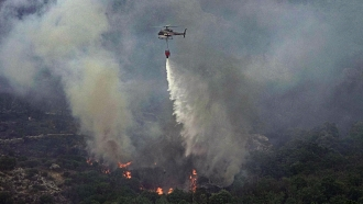 A helicopter drops water to put out flames on the island of Sardinia, Italy.