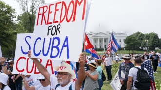 """Jose Estevez, of Miami, holds a sign saying """"Freedom for Cuba,"""" as hundreds of people protest the Cuban government"""