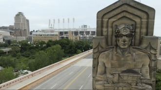 Statue stands in front of a stadium.