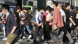 People wearing face masks to protect against the spread of the coronavirus walk on a street in Tokyo.