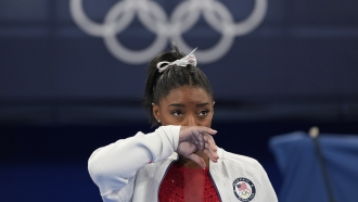 Simone Biles, of the United States, watches gymnasts perform at the 2020 Summer Olympics