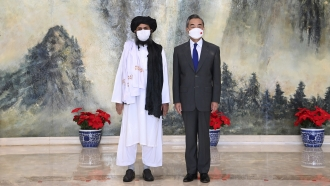 Taliban co-founder Mullah Abdul Ghani Baradar, left, and Chinese Foreign Minister Wang Yi, right