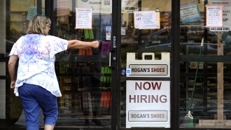 A hiring sign is displayed outside a retail store in Buffalo Grove, Ill.