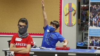 File photo: Texas student wears a mask and raises hand