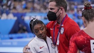 Coach Laurent Landi embraces Simone Biles, after she exited the team final