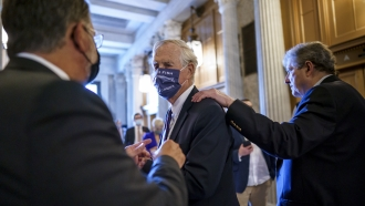Sen. Angus King, I-Maine, center, speaks with Sen. Gary Peters, D-Mich., left.