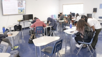 Students work in a classroom.