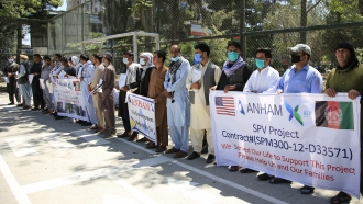 Former workers who had been employed with U.S. troops at the Bagram airbase hold placards during a demonstration.