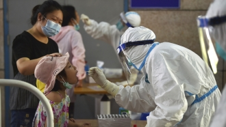 A nurse takes swab samples in the new rounds of Covid-19 testing in Nanjing in eastern China
